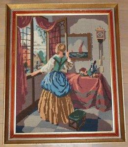 Groot borduurwerk dame kijkt uit raam in oude lijst
